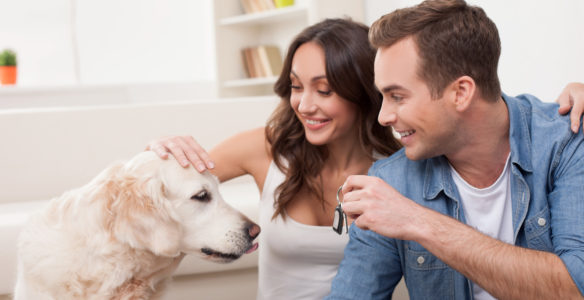 Cheerful young family is moving in new apartment. They are sitting on flooring with joy. The man is showing a key to a dog. The married couple is embracing and smiling