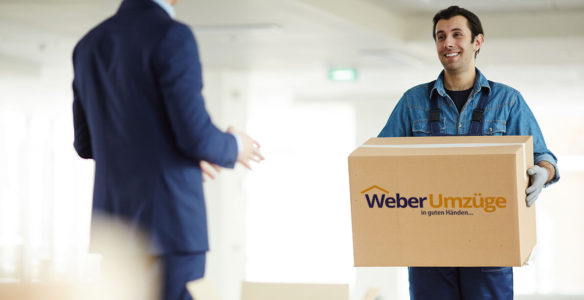 Young courier carrying big box to office worker while helping him to relocate