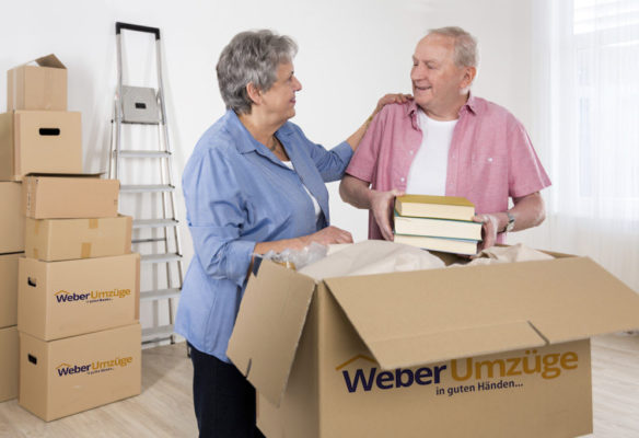 Senior adult couple unpacking books in their new home